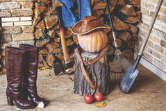 Autumn Still Life. Pumpkin, tool, wood, hat, boots on porch Royalty Free Stock Images
