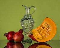 Autumn still life with pumpkin and two pomegranate. Stock Photography