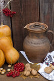 Autumn still life with pumpkins and autumn berry and vegetables on old wooden background, closeup Stock Photo