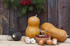 Autumn still life with pumpkins and autumn berry and vegetables on old wooden background, closeup. Selective focus Royalty Free Stock Photo