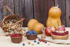 Autumn still life with pumpkins and autumn berry and vegetables on old wooden background, closeup. Selective focus Stock Photo