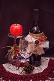 Autumn still-life with red wine, rowan and apple Royalty Free Stock Image