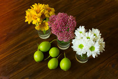 Autumn still life. Ripe pears, rustic wooden table, flowers in vase. autumn still life. still life with colorful autumn flowers and pears Royalty Free Stock Images