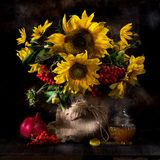 Autumn Still life with sunflowers. Honey and fruits Stock Image