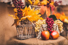 Autumn still life at the table covered with burlap. Apples, grapes, yellow leaves and berries in vase Stock Photography