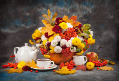 Autumn still life. Tea, flower and yellow leaves Stock Images