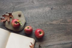 Autumn still life with three apples, open book and leaves over rustic wooden background. Horizontal, copy space Royalty Free Stock Photo