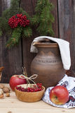 Autumn still life in Ukrainian style clay pot and autumn berry and vegetables on old wooden background, closeup. Selective focus Stock Photo