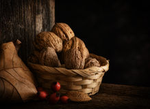 Autumn Still Life with Walnut, Leaf and Rosehip. Wooden Background, and braided Basket stock photo