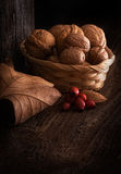 Autumn Still Life with Walnut, Leaf and Rosehip. Wooden Background, and braided Basket stock image