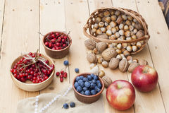 Autumn still life with walnuts and hazelnuts in the basket and autumn berry and vegetables on old wooden background, closeup Stock Photo