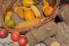 Autumn still life. Wicker basket with corn, pumpkins, red apples and wood logs exposed at city fair stock image