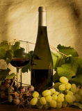 Autumn still life with wine and grapes. Bottle and cup of red wine with grapes Royalty Free Stock Image