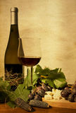 Autumn still life with wine and grapes. Bottle and cup of red wine with grapes Stock Photo