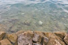 Autumn stone lake shore with transparent water closeup Royalty Free Stock Photo