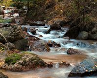 Autumn Stream. A slow flowing stream cutting through the rocks framed by Autumn foliage Stock Photo