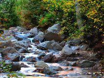 Autumn Stream at Sunrise. A slow flowing stream cutting through the rocks framed by Autumn foliage royalty free stock image