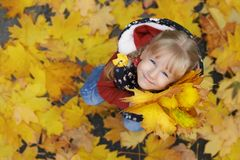 Autumn street portrait of the little girl holding a bunch of maple leaves