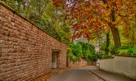 Autumn street with a stone wall stock images