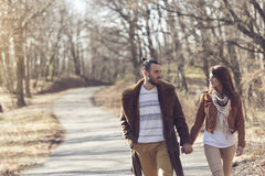 Autumn stroll through the forest. Couple holding hands and walking down the road through a forest, enjoying a sunny spring day stock images