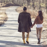 Autumn stroll through the forest. Couple holding hands and walking down the road through a forest, enjoying a sunny spring day stock photos