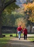 Autumn stroll in the park. Couple of seniors enjoying autumn day Stock Images