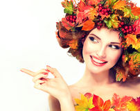 Autumn style, bright makeup, red manicure and lipstick. Autumn Beauty. Red and yellow autumn leaves and red berry in wreath on girl head royalty free stock photo