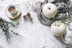 Autumn styled photo. Feminine Halloween desktop scene. Cup of coffee, eucalyptus, pine cones, white pumpkins and