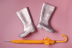Umbrella and rain boots on pink royalty free stock photo