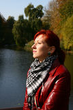 Autumn sun enjoyment. Beautiful woman with red hair and dressed red jacket enjoy autumn sun on the riverside Royalty Free Stock Images