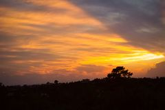 Autumn Sun set, golden / orange colours light up the sky though the cloudscape royalty free stock photo