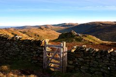 Wooden gate and the summit of High Pike. Autumn sunlight on the northern fell summits Royalty Free Stock Image