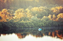 Autumn sunny landscape-birds eye view of autumn yellowed forest and river with boat at early autumn morning Stock Images