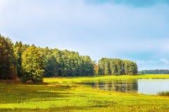 Autumn sunny landscape of Soroti river and autumn yellowed forest trees in Pushkinskiye Gory, Russia. Autumn sunny view of autumn forest near the Soroti river Stock Photo