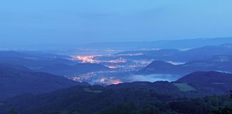 Autumn sunrise above industry town in  Bohemia. Peaks of hills increased from foggy background. Royalty Free Stock Photo
