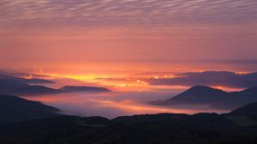 Autumn sunrise above industry town in  Bohemia. Peaks of hills increased from foggy background. Stock Images
