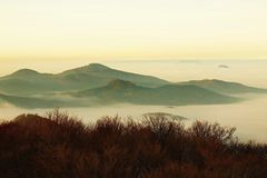 Autumn sunrise in a beautiful mountain of Bohemia. Peaks of hills increased from fog. Royalty Free Stock Photos