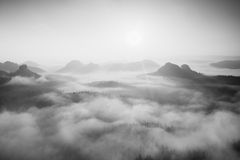 Autumn sunrise in a beautiful mountain within inversion. Peaks of hills increased from foggy background. Black and white photo. Stock Image