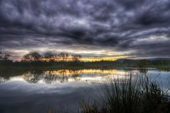 Autumn sunrise over a lake. Autumn sunrise and dramatic clouds over a lake in the countryside Stock Photo