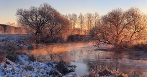 Frozen river in the morning. Bright sun shines though trees. Frozen river in the morning Royalty Free Stock Image