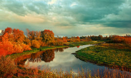 Autumn sunset landscape with river and yellowed tress. Autumn colorful view - sunset autumn picturesque landscape with autumn river and yellowed autumn trees in Royalty Free Stock Photo