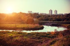 Autumn sunset landscape with yellow and green trees and river. Fall park in Minsk, Belarus. Plain nature area. Wirh river and park in big city. City recreation stock photography