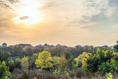 Autumn sunset over the roofs of suburban houses. Evening landscape in backlight sunlight. Stock Image