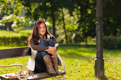 Autumn sunset park woman sitting on bench Stock Photo