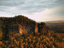 Autumn sunset view over sandstone rocks to fall colorful valley of Bohemian Switzerland. Sandstone peaks in forest. Stock Image