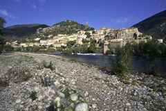Picturesque France - Roquebrun. Autumn sunshine on the idyllic hillside village of Roquebrun on the River Orb, Herault, Languedoc-Roussillon, France royalty free stock photos