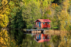 Autumn in Sweden. Traditional red little cabin at lake in October Royalty Free Stock Photos