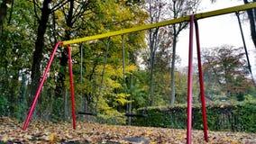 Autumn Swings nel campo da giuoco dei bambini Fotografia Stock Libera da Diritti