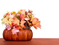 Autumn Table. Autumn centerpiece of leaves and berries in a basket on brown table cloth Royalty Free Stock Images