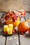 Autumn table decoration: bouquet in pumpkin and candles Stock Images
